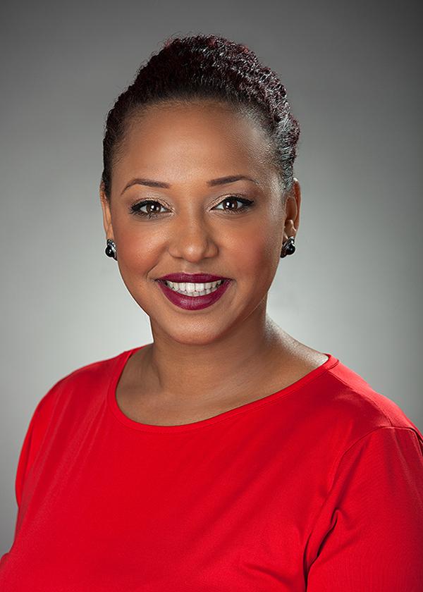 Bewerbungsfoto einer lächelnden Frau in rotem Oberteil